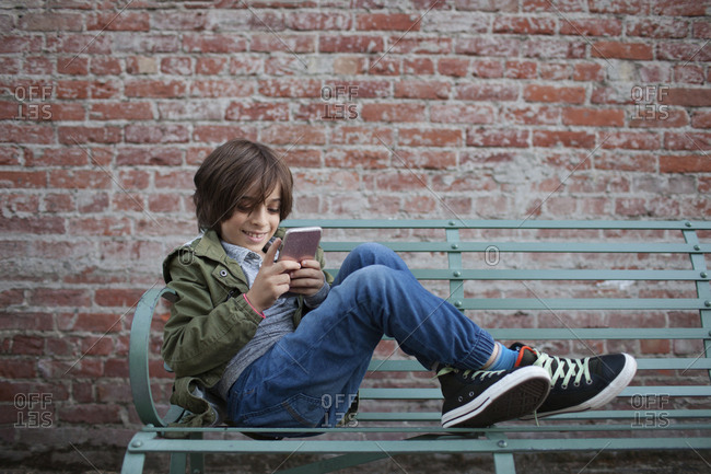 Full length of smiling boy using smart phone while sitting on bench against brick wall at footpath
