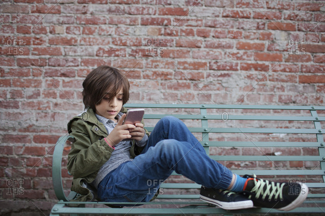 Full length of boy using smart phone while sitting on bench against brick wall at footpath