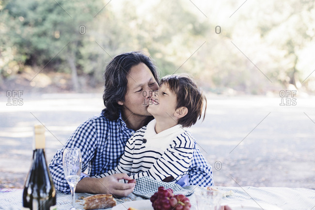 Loving father kissing son while sitting at table with food in park
