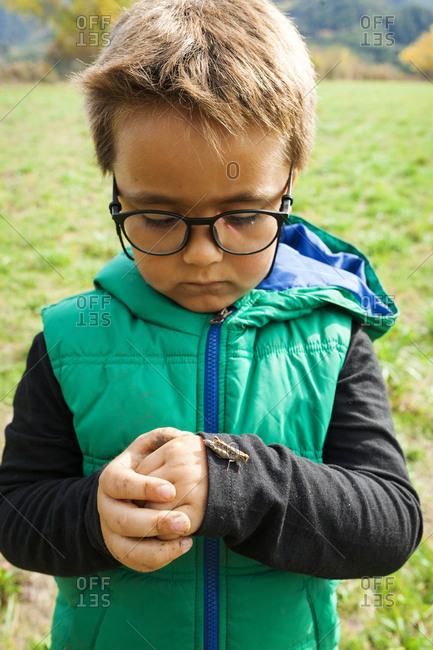 Serious boy looking at grasshopper on hand while standing in park