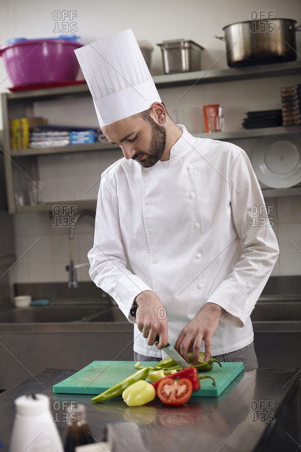 Chef chopping vegetables on cutting board at commercial kitchen