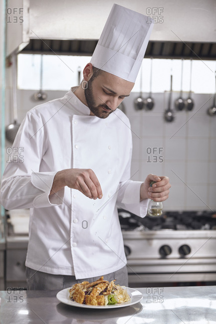 Chef sprinkling seasoning on food in plate at commercial kitchen