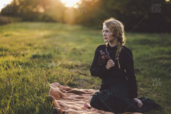 Thoughtful young woman with braided hair looking away while sitting on blanket in grassy field