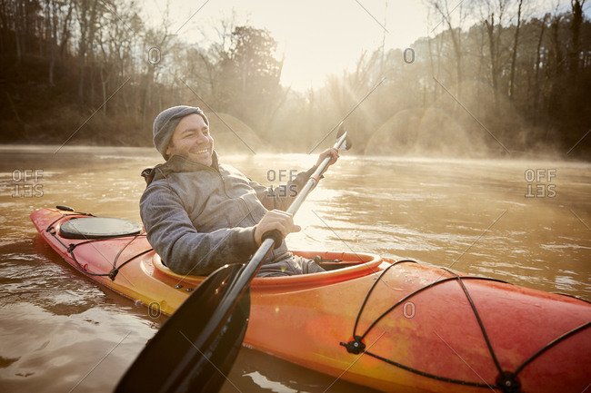 Smiling man kayaking on Chattahoochee River against sky