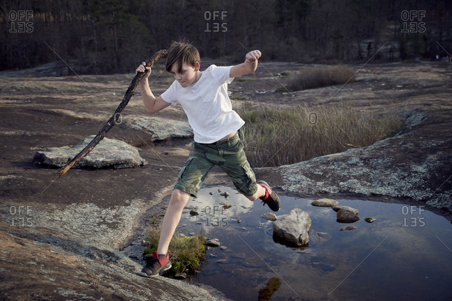 Boy jumping over puddle on Arabia Mountain