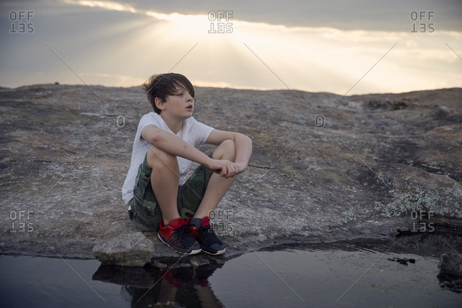 Boy looking away while sitting by stream on Arabia Mountain against cloudy sky