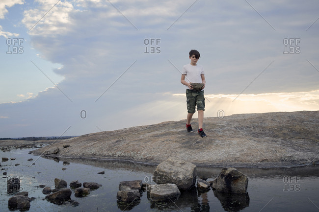 Boy carrying rocks while walking on Arabia Mountain against cloudy sky
