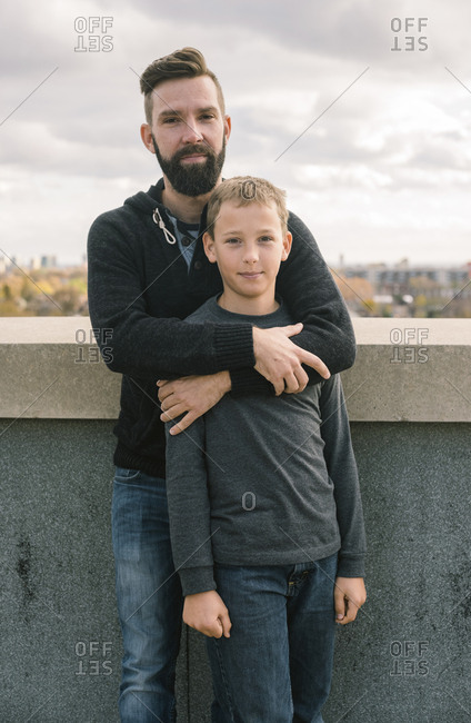 Portrait of smiling father with son standing by retaining wall against cloudy sky