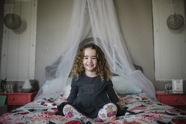 Portrait of cheerful girl sitting on bed at home