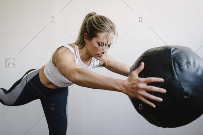 Woman carrying fitness ball while standing by wall in gym