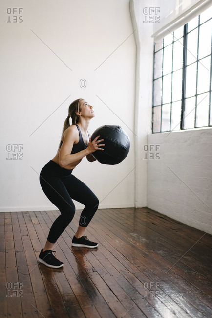 Female athlete carrying fitness ball while standing in gym