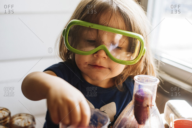 Close-up of girl wearing protective eyewear while holding food at home