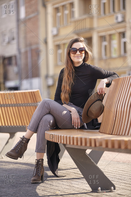 Woman wearing sunglasses sitting on bench in city