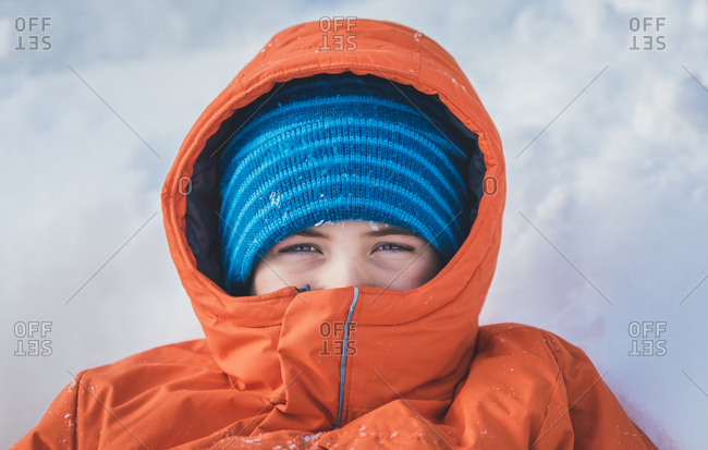 High angle portrait of boy in warm clothing lying on snow covered field