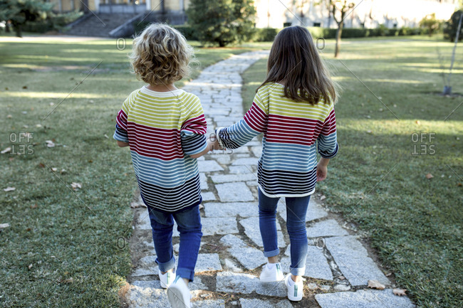 Rear view of sisters walking on footpath at park