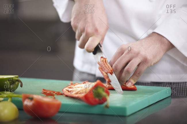 Midsection of chef chopping red jalapeno pepper on cutting board at commercial kitchen