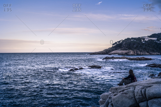 Woman looking at sea while sitting on rocks against sky during sunset