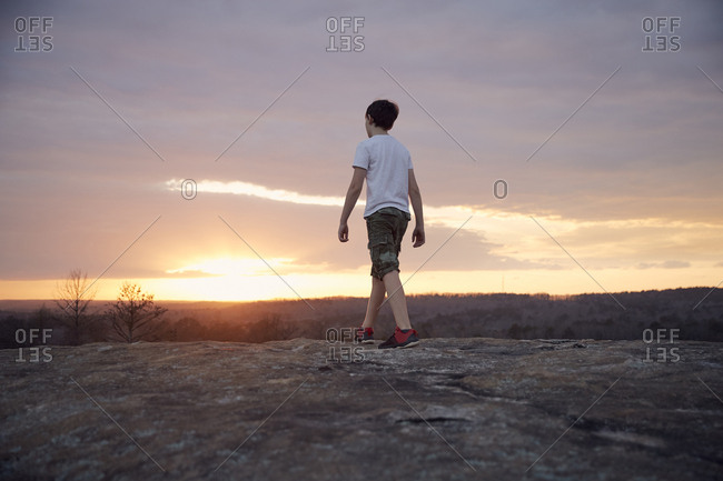 Rear view of boy walking on Arabia Mountain against cloudy sky during sunset