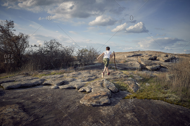 Rear view of boy holding stick while running on Arabia Mountain against sky