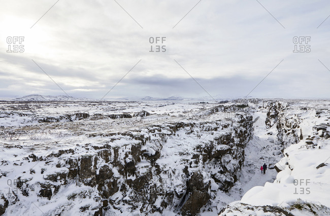 Distant view of father and daughter amidst snow covered rock formations against sky