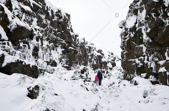 Mid distance view of father and daughter walking amidst snow covered rocks