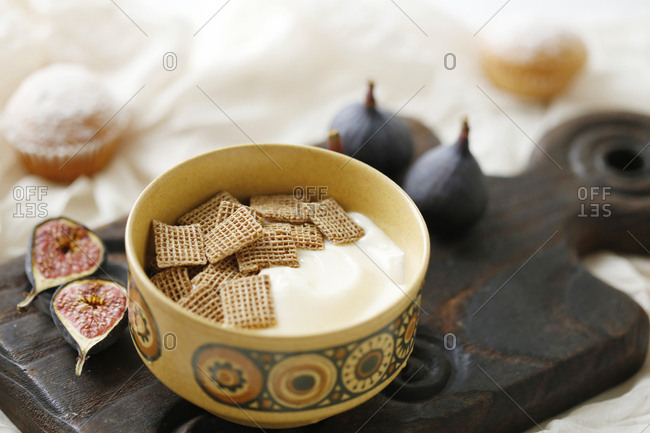 High angle view of vanilla yogurt with crackers in bowl by figs on cutting board