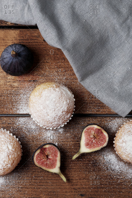 Overhead view of muffins with figs and napkin on wooden table