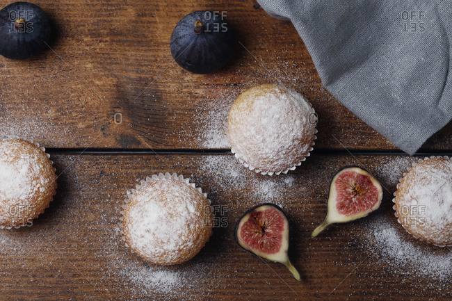 Overhead view of muffins with figs by napkin on wooden table