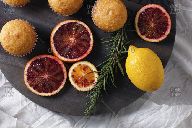 High angle view of fairy cakes with rosemary and citrus fruits on cutting board
