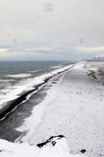 Scenic view of sea against cloudy sky during winter