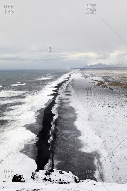 Idyllic view of sea against cloudy sky during winter