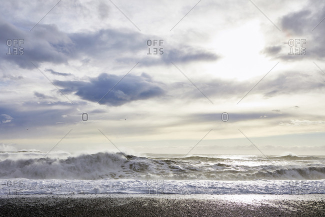 View of waves on shore against cloudy sky