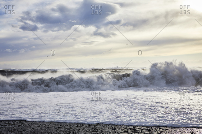 Scenic view of waves on shore against cloudy sky