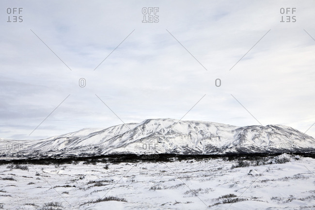 Tranquil view of snowcapped mountains against cloudy sky