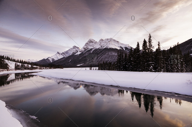 Scenic view of lake by snow covered landscape against sky during sunset
