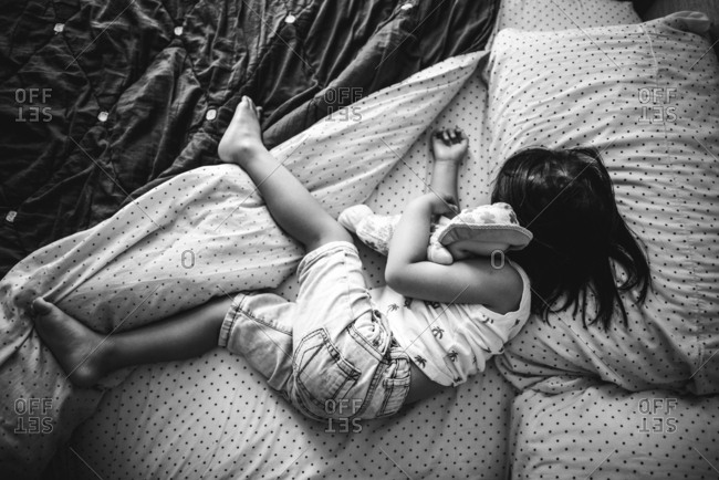 Toddler sleeping with a doll on a bed