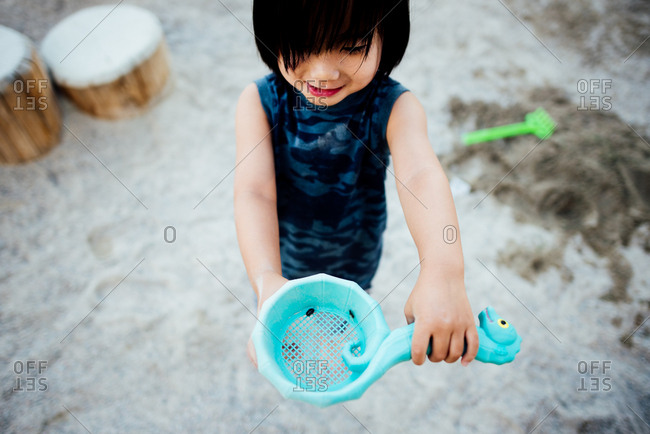 Toddler showing off bugs in a shovel at the sandbox