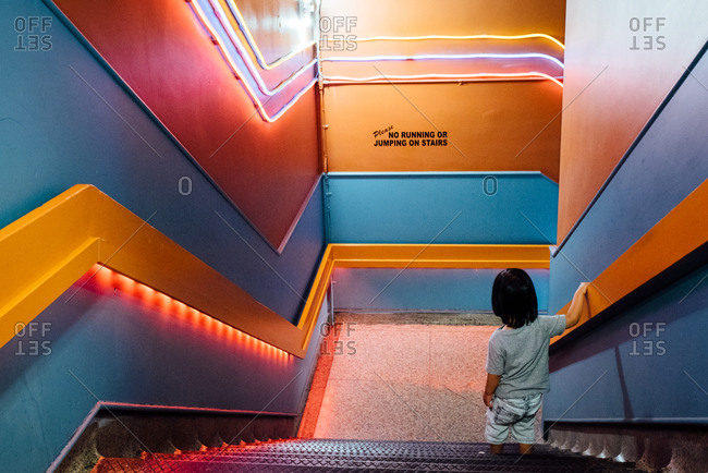 Toddler going down stairwell with colorful walls