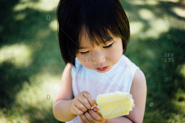 Toddler eating a yellow popsicle