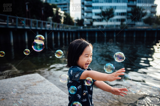 Happy toddler popping bubbles