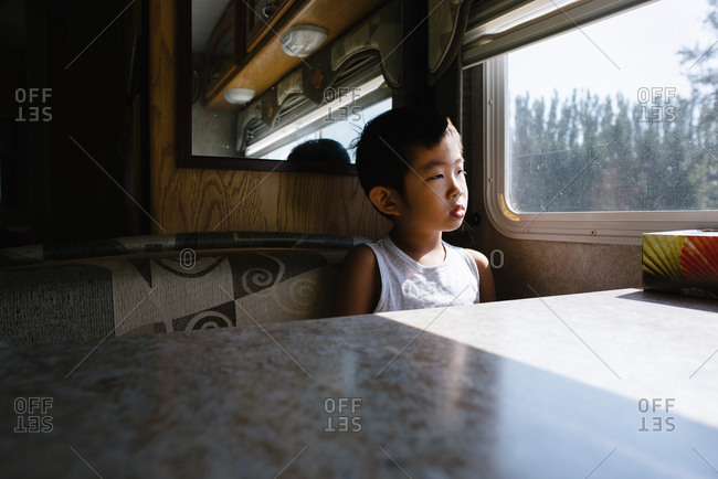 Boy looking out of a window in an RV