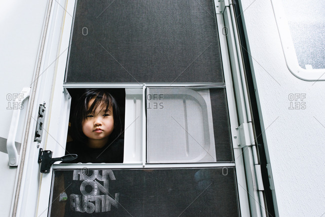 Toddler looking out of a window of an RV