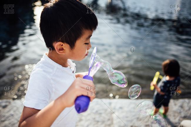 Boy blowing bubbles outside