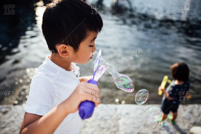Boy blowing bubbles outside