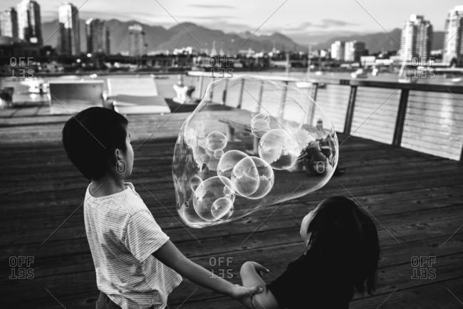 Boys blowing bubbles outside