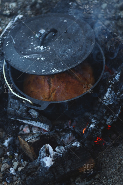 Bread baking in a cast iron pot over camp fire