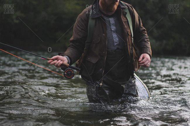 Fisherman holding fly rod looking for trout in thigh deep water