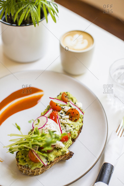 High angle view of avocado toast served with a cafe latte