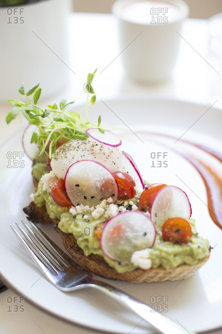 Close up of avocado toast with sliced radishes and cherry tomatoes