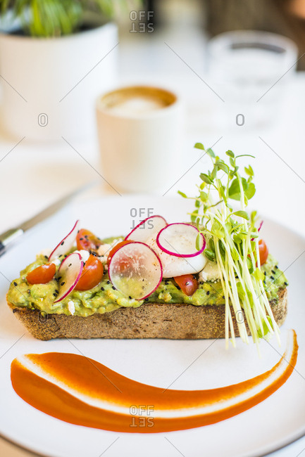 View of avocado toast served on plate with decorative flourish